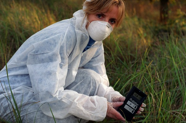 Adi holds a Geiger counter in the exclusion zone, close to the Chernobyl nuclear power plant. Picture by Julien Behal (2003)