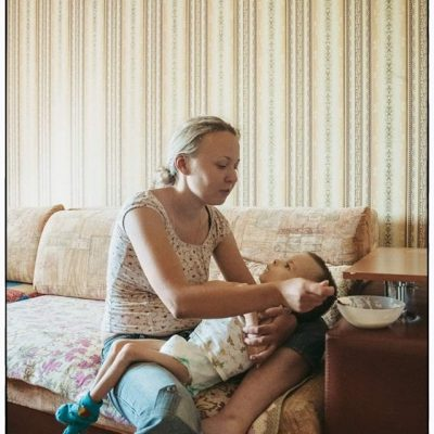 Mother feeding high dependency child